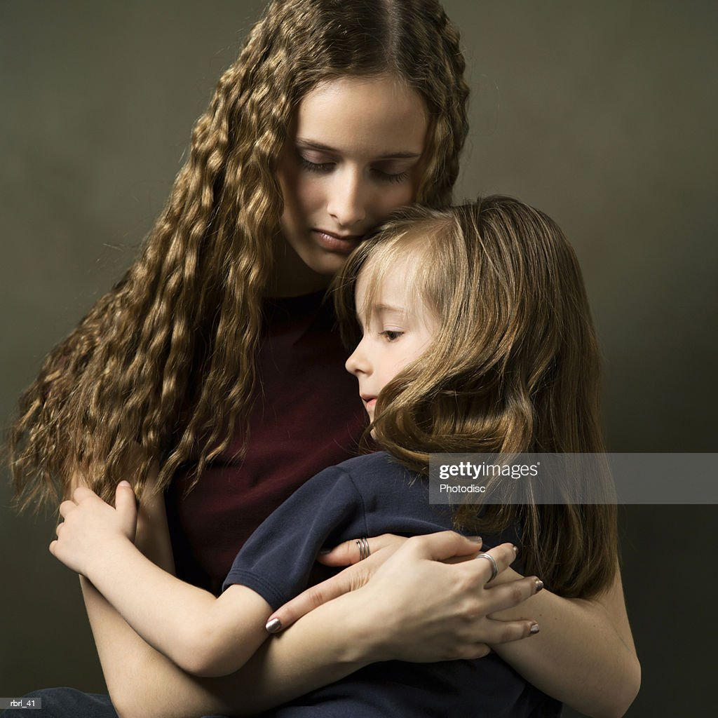 a caucasian teenage girl lovingly embraces her little sister : Foto de stock