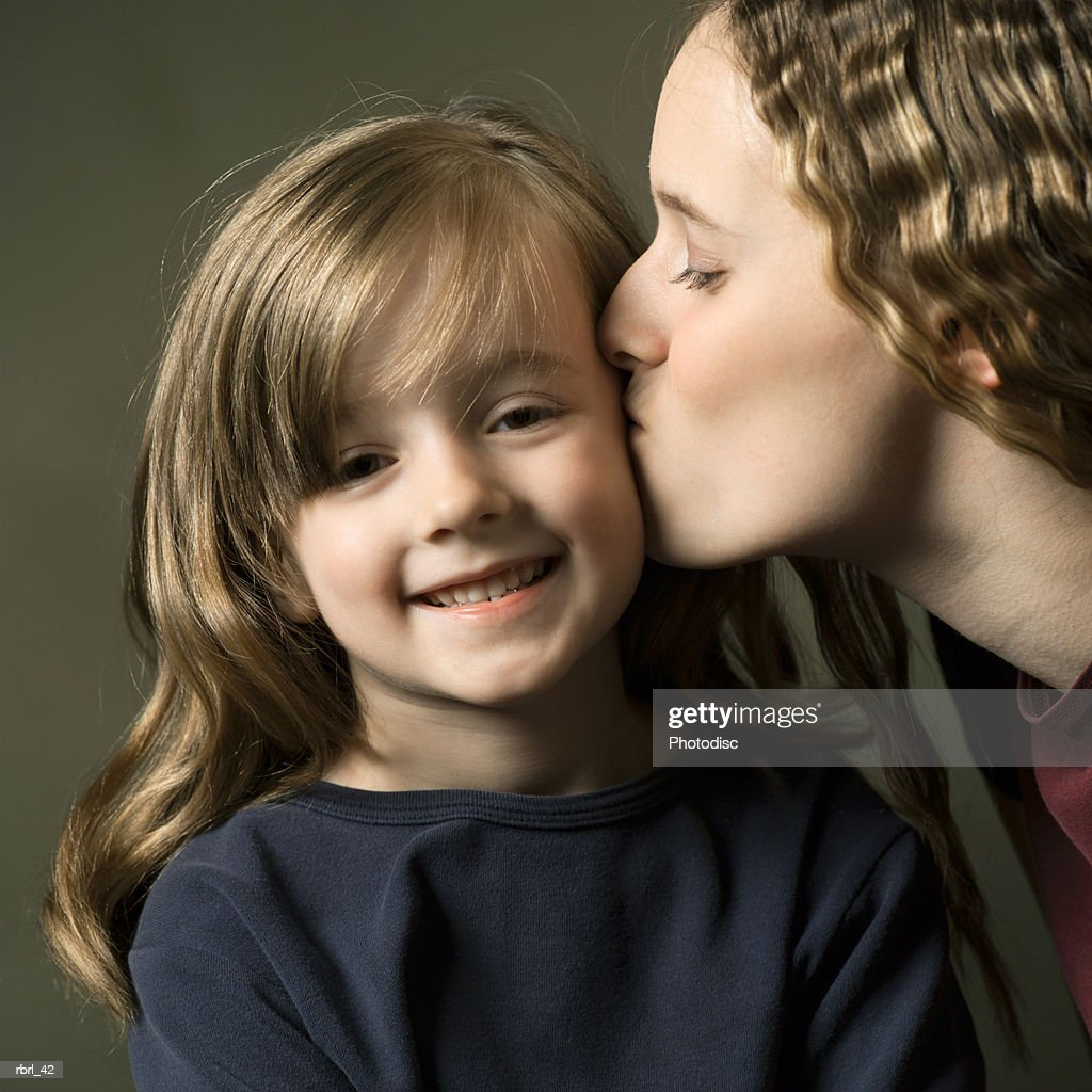 a caucasian teenage girl lovingly kisses her little sister on the cheek : Foto de stock