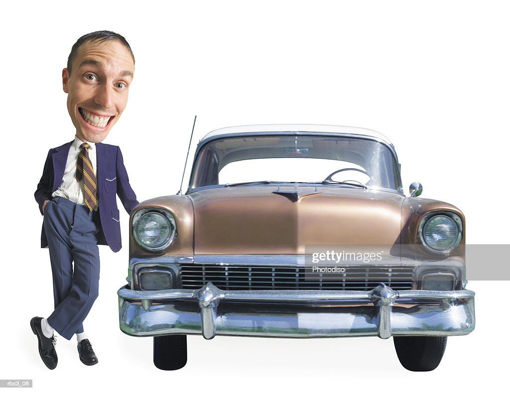 a caucasian used car salesman leans on an old used car and smiles cheesily at the camera : Stockfoto