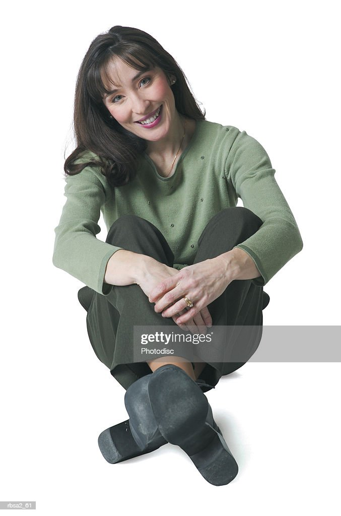 a caucasian woman dressed in green pants and blouse sits down and smiles : Foto de stock