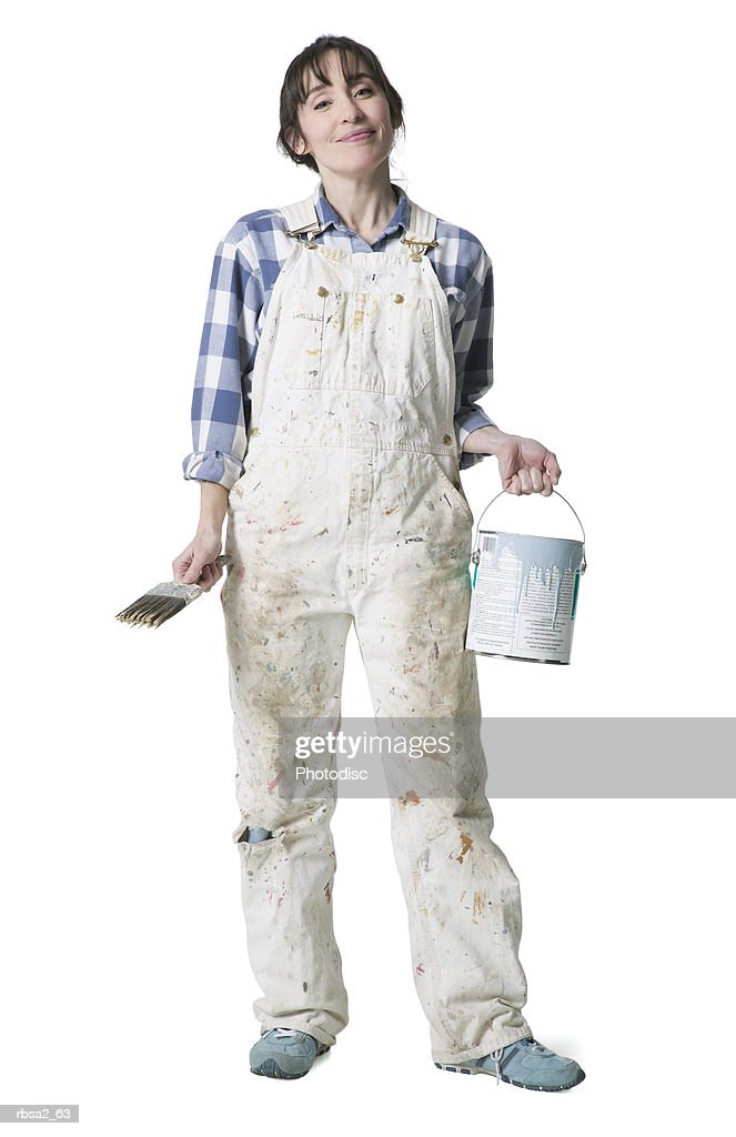 a caucasian woman dressed in overalls smiles as she holds a paint brush and paint bucket : Foto de stock