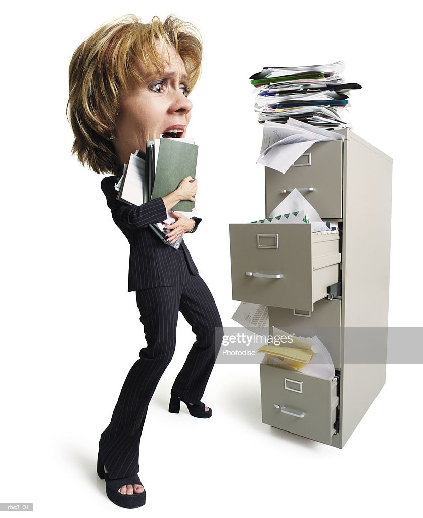 a caucasian woman holding a stack of files stands in front of an overfilled file cabinet looking overwhelmed at all of the papers : Stockfoto