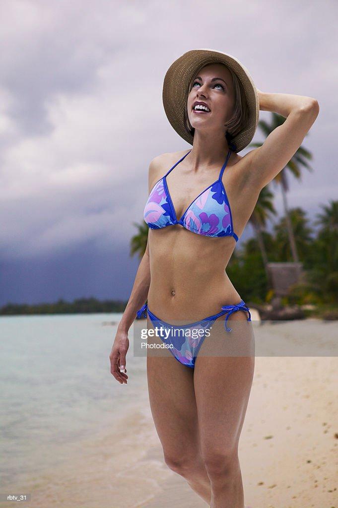 a caucasian woman in a bikini and hat walks along a beach in the tropics : Foto de stock