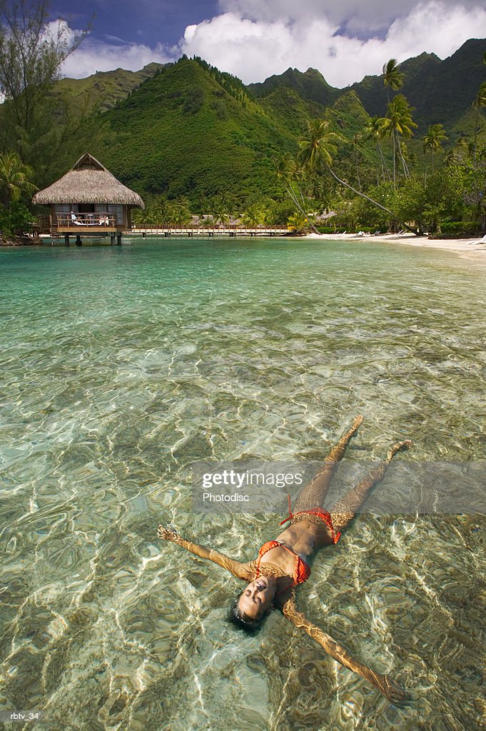a caucasian woman in a bikini floats on her back in the clear water as she vacations at a tropical resort : Foto de stock