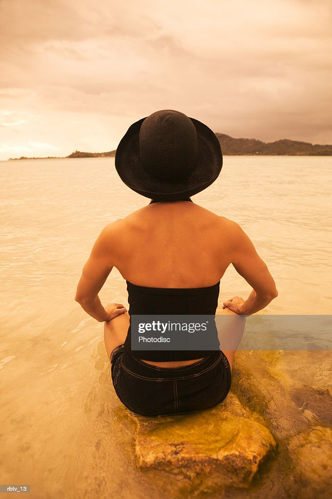 a caucasian woman in a black hat sits in the water on a beach in a tropical setting : Foto de stock