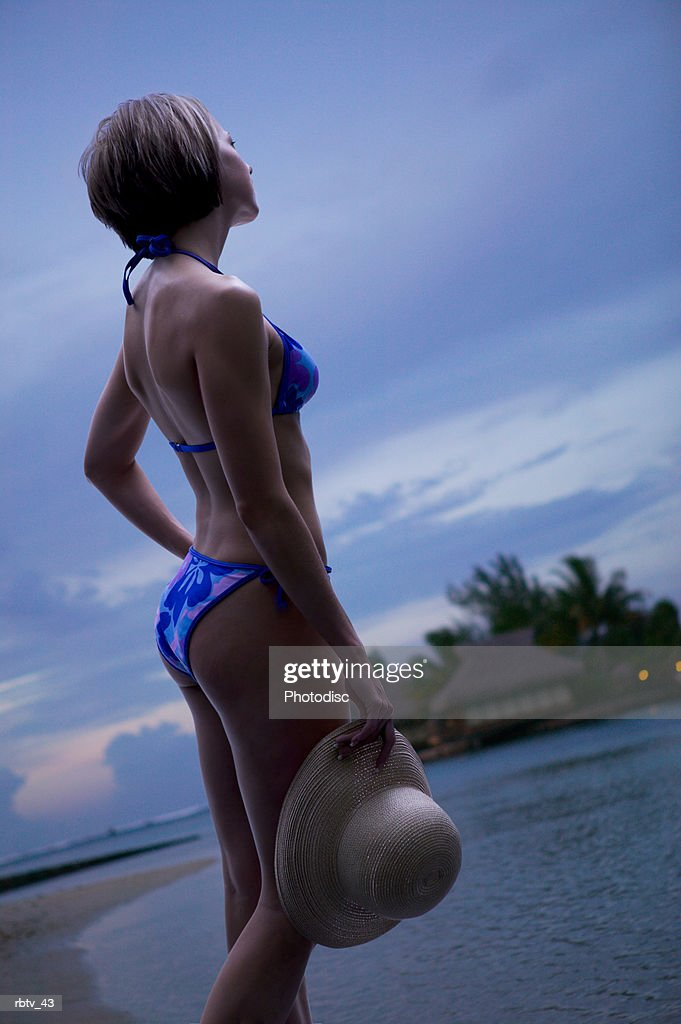 a caucasian woman in a blue bikini holds her hat and stands overlooking the beach : Foto de stock