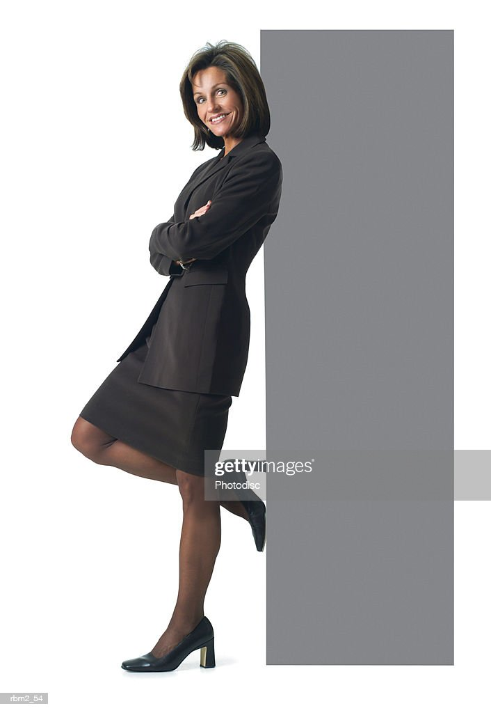 a caucasian woman in a brown business outfit leans her back against a large sign : Stockfoto