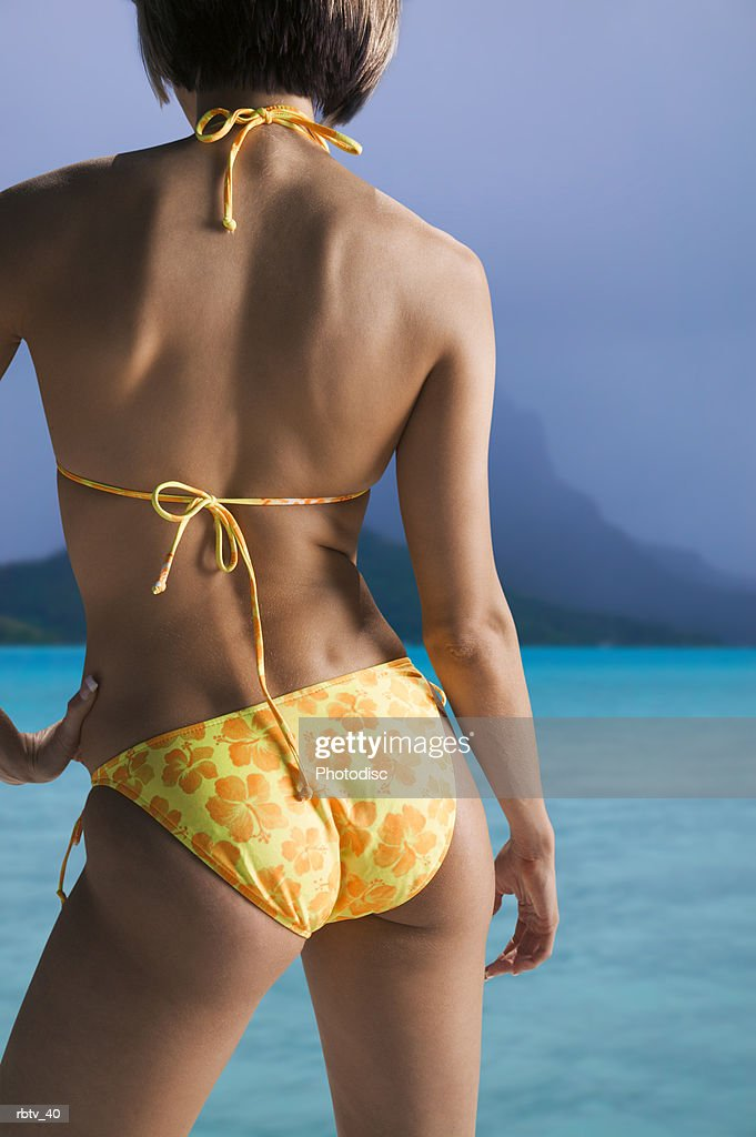 a caucasian woman in a yellow bikini looks out over the clear water on a beach : Foto de stock