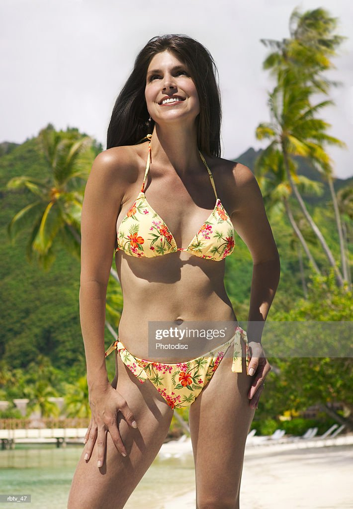 a caucasian woman in a yellow bikini stand in the sun on a tropical beach : Foto de stock