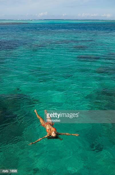 a caucasian woman in an orange bikini floats in a blue lagoon at a beautiful beach