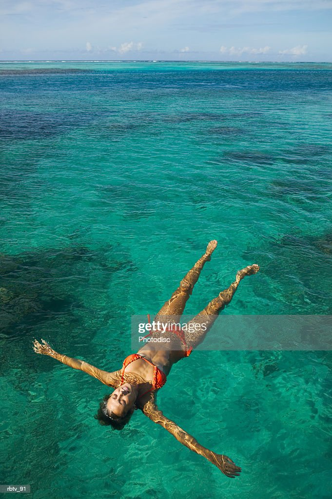a caucasian woman in an orange bikini floats on her back through the crystal clear water of the tropics : Foto de stock