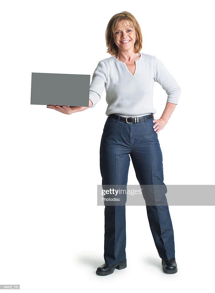a caucasian woman in blue pants and a grey blouse holds a  sign in the palm of her hand : Stockfoto