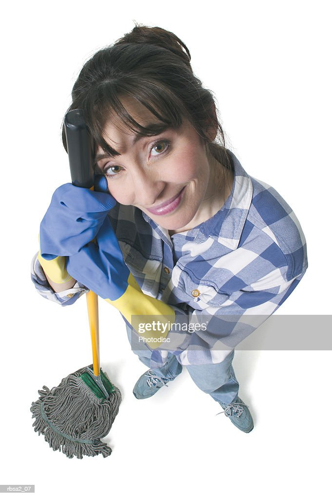 a caucasian woman in jeans and a plaid shirt wears rubber gloves and holds a mop as she looks up into the camera : Foto de stock