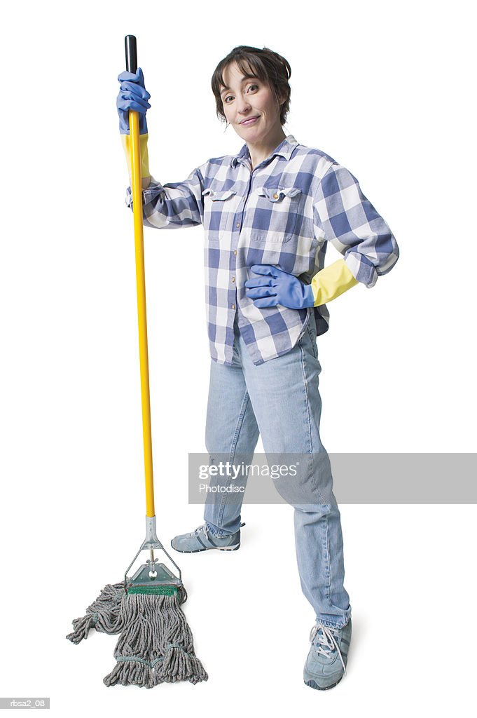 a caucasian woman in jeans and a plaid shirt wears rubber gloves and holds a mop : Stock Photo