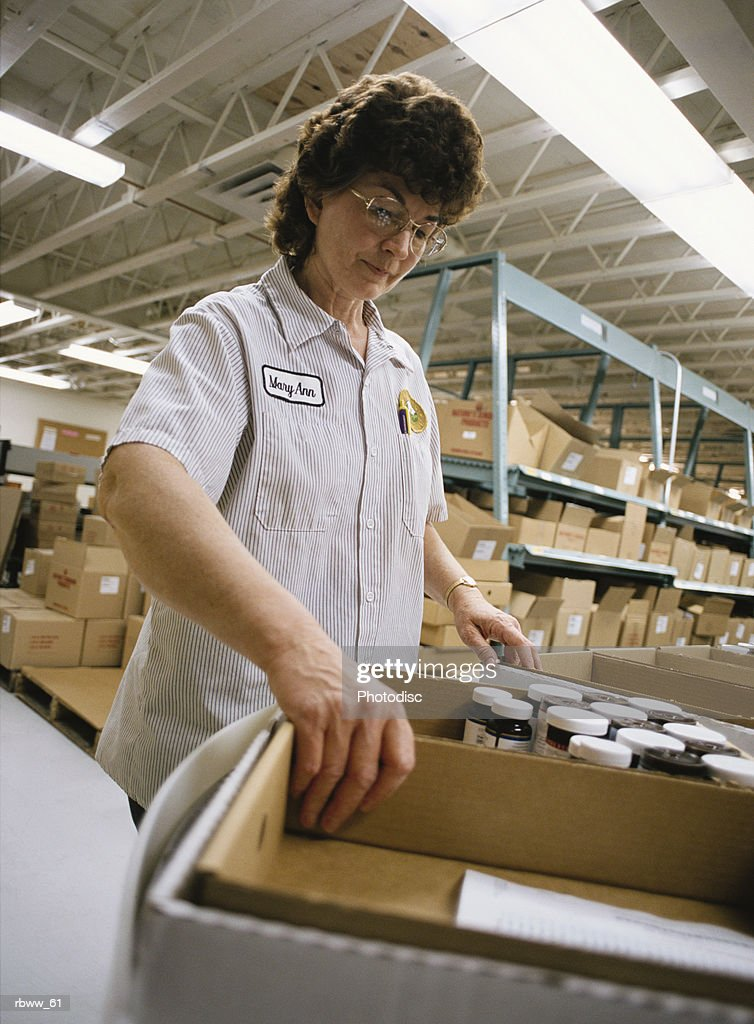 a caucasian woman lifts a box of pill bottles at a warehouse : Stockfoto
