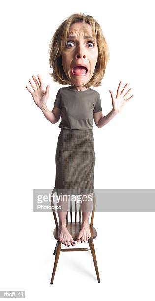 a caucasian woman stands on a chair wearing an expression of great fear