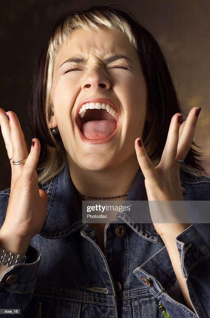 a caucasian young woman with brown and blond streaked hair wearing a jean jacket is screaming with eyes closed and hands raised near her face : Stockfoto