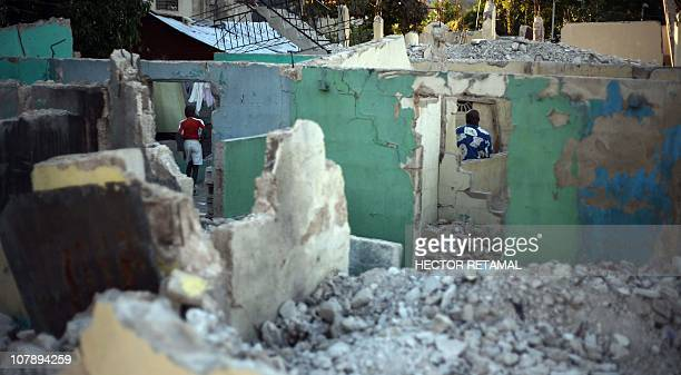 A child and an adult are seen inside their dwellings amid rubble on January 5, 2011 in Port-au-Prince. One year after Haiti's earthquake, only five...