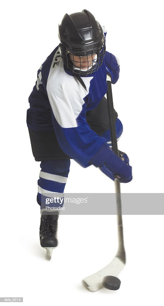 a child caucasian male hockey player dressed  in a blue white and black jersey skates with his stick and puck : Stockfoto