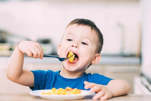 a child in a t-shirt in the kitchen eating an omelet, a fork 1160049332
