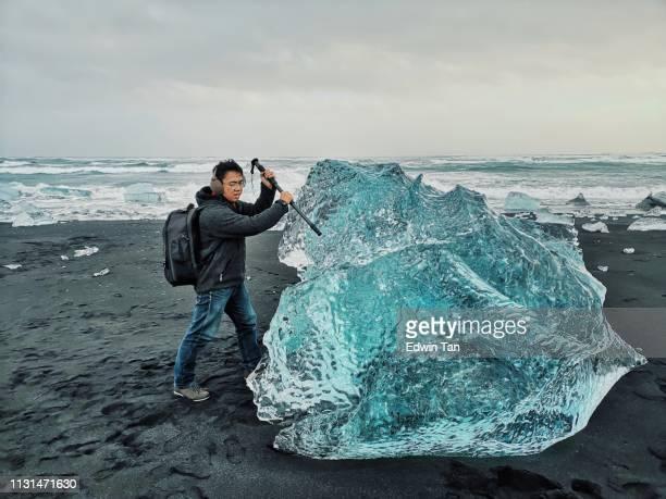 un mâle chinois pointe son monopode sur l'iceberg à diamond beach en islande - froid humour photos et images de collection
