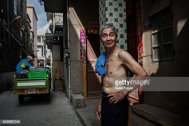a Chinese man stands in an alleyway of a village on Shazai Island where the Sun YatSen UniversityMichigan University Joint Center of Vector Control...