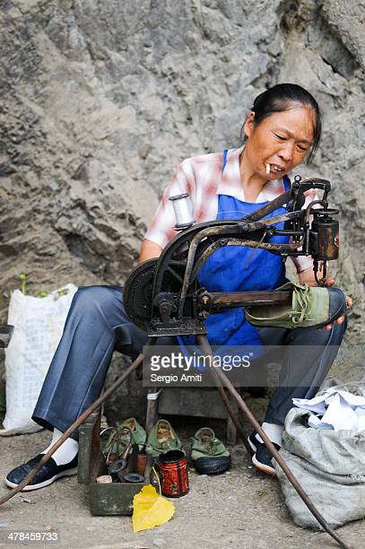 CONTENT] a Chinese woman mending shoes in a village in the Chinese countryside