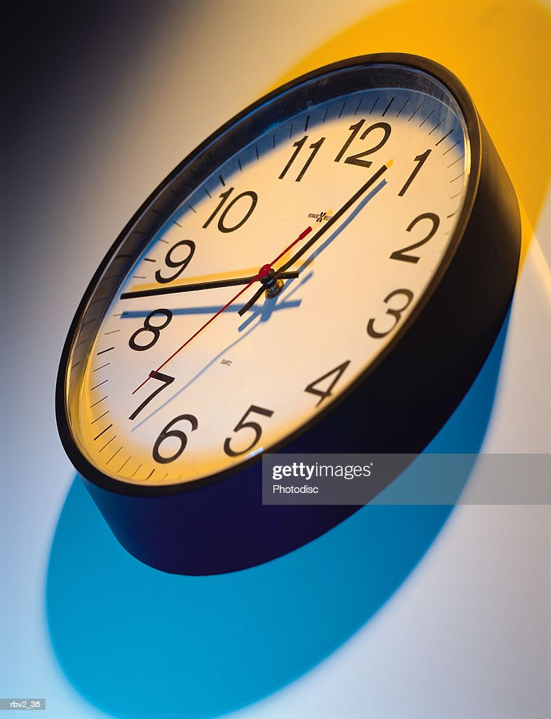 a clock on a white surface cast blue and yellow shadows : Foto de stock