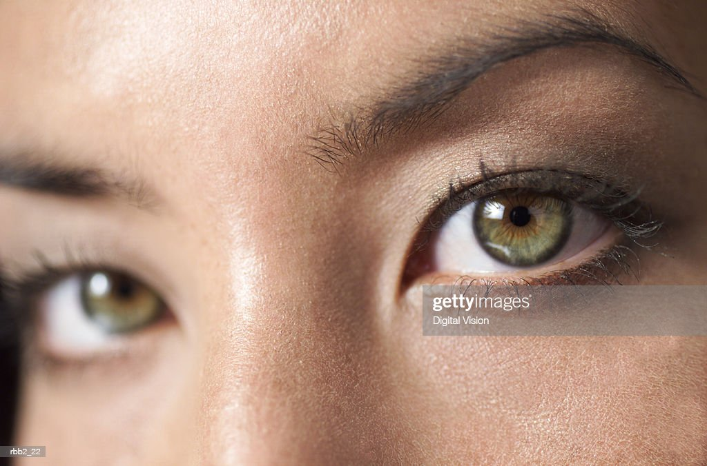 a close up shot of a the beautiful green eyes of a young attractive ethnic girl : Stock Photo