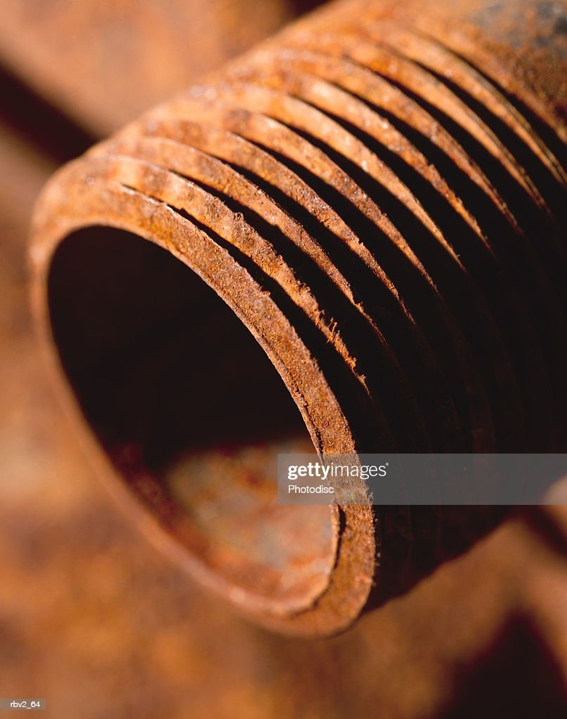 a close-up of a rusted steel pipe lying on other rusted steel pipes : Stockfoto