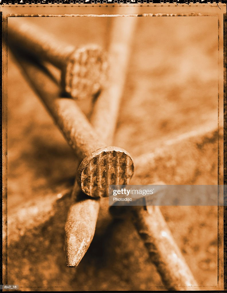a close-up of rusted nails laying together on the ground : Foto de stock