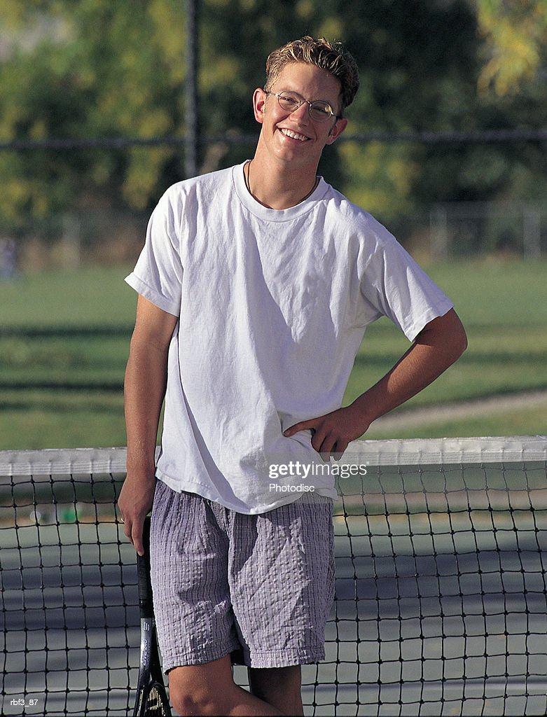 a college-aged man wearing a white shirt and glasses places a hand on his hip as he holds a tennis racket while standing in a tennis court : Stockfoto