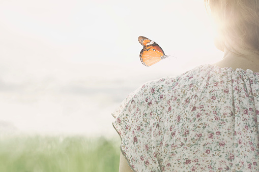 a colorful butterfly leans delicately on the shoulders of a girl 1071291568