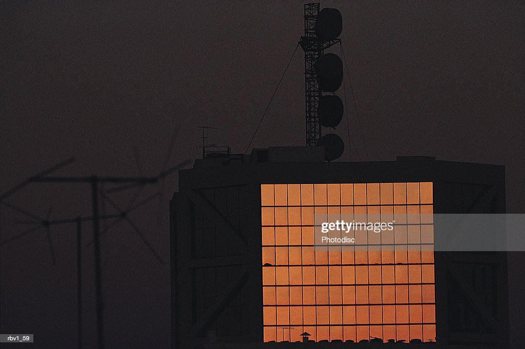a communications tower with its antennae and large glass windows rises in a dark sky : Foto de stock