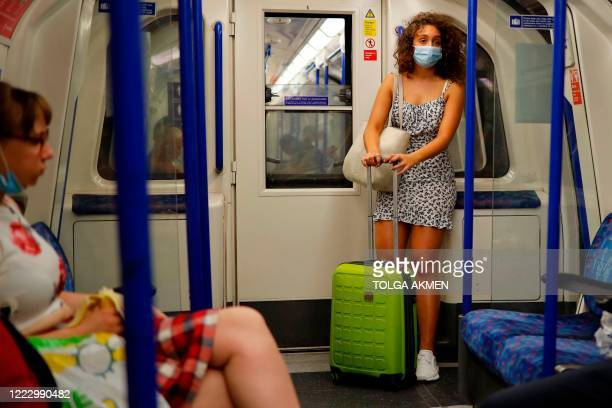 A commuter wears a facemask as she travels on the tube in London on June 26, 2020. - Britons were on Friday urged to abide by social distancing rules...