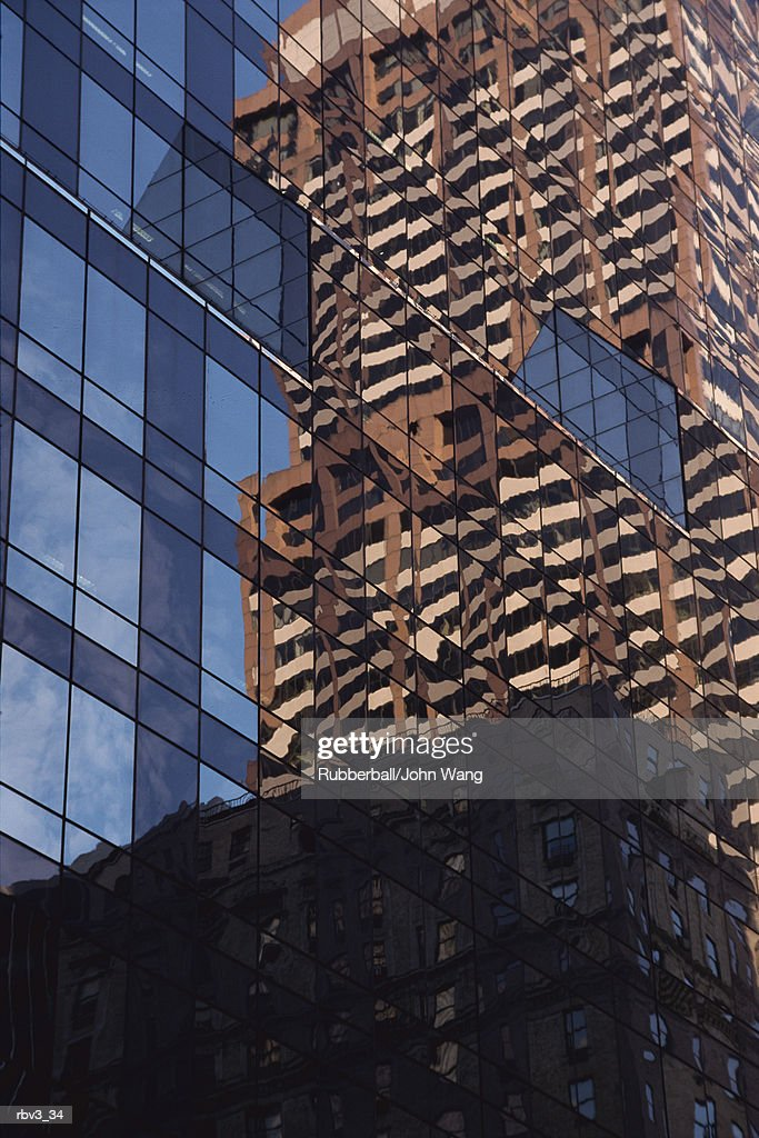 a corporate black glassed building reflects a large brown and tan skyscraper and the sky : Foto de stock