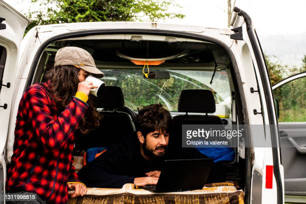 a couple enjoying life in a van, the man looks at his laptop and the woman has a cup of tea. - boot stock pictures, royalty-free photos & images