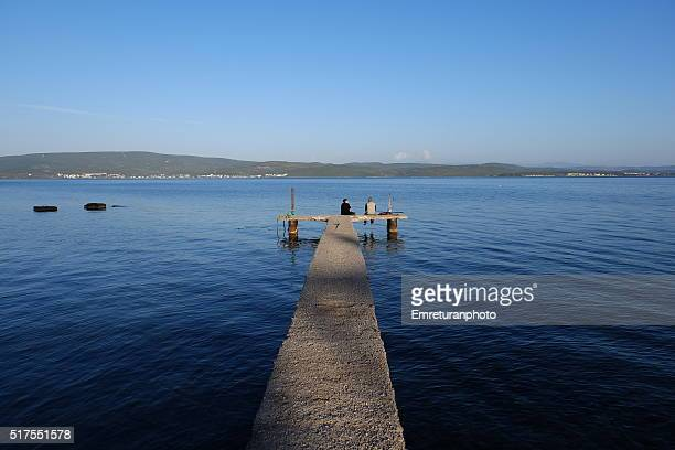 a couple sitting at the end of a wooden pier - emreturanphoto stock pictures, royalty-free photos & images