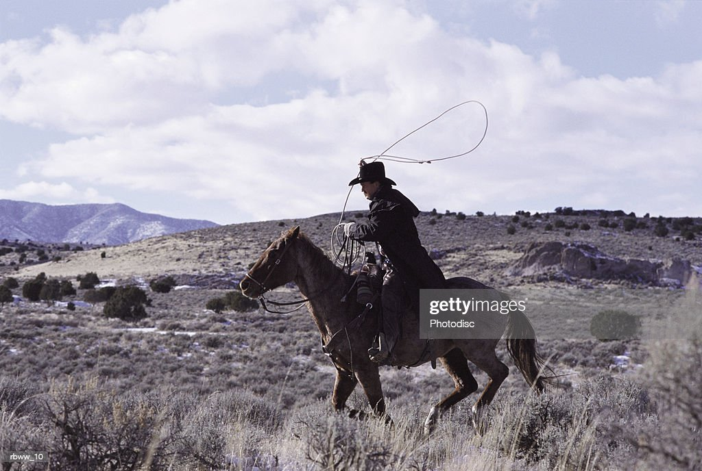 a cowboy rides his horse : Foto de stock