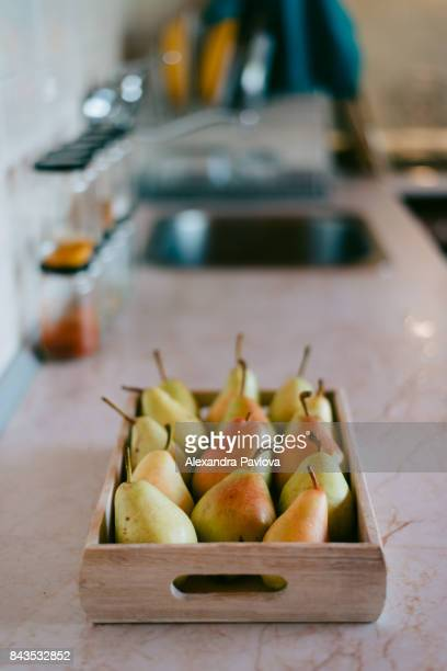 a crate of ripe pears in cozy kitchen interior