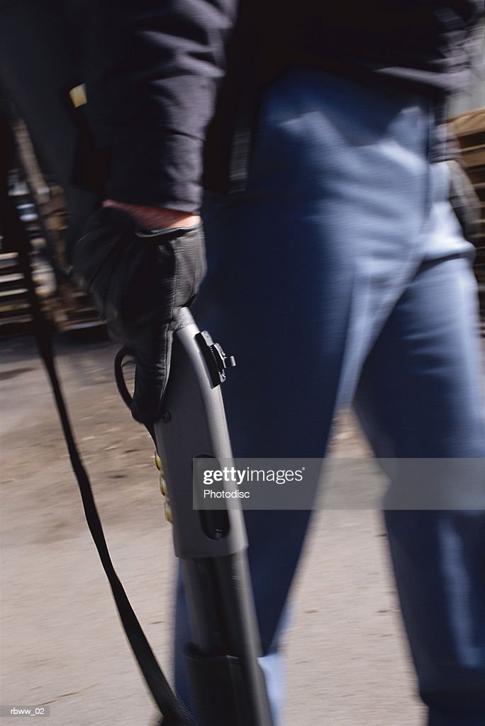 a cropped abstract image of a man wielding a shotgun : Stockfoto