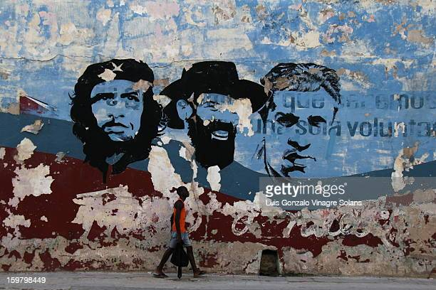 A cuban walks by a mural in an advanced state of decay depicting famous revolutionaries: the che guevara, camilo cienfuegos and julio antonio mella ....
