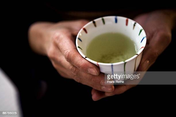 a cup with green tea hold with hands