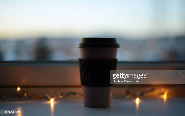 a cup with warm drink in a windowsill by a chain of christmas lights - kristina strasunske stock pictures, royalty-free photos & images