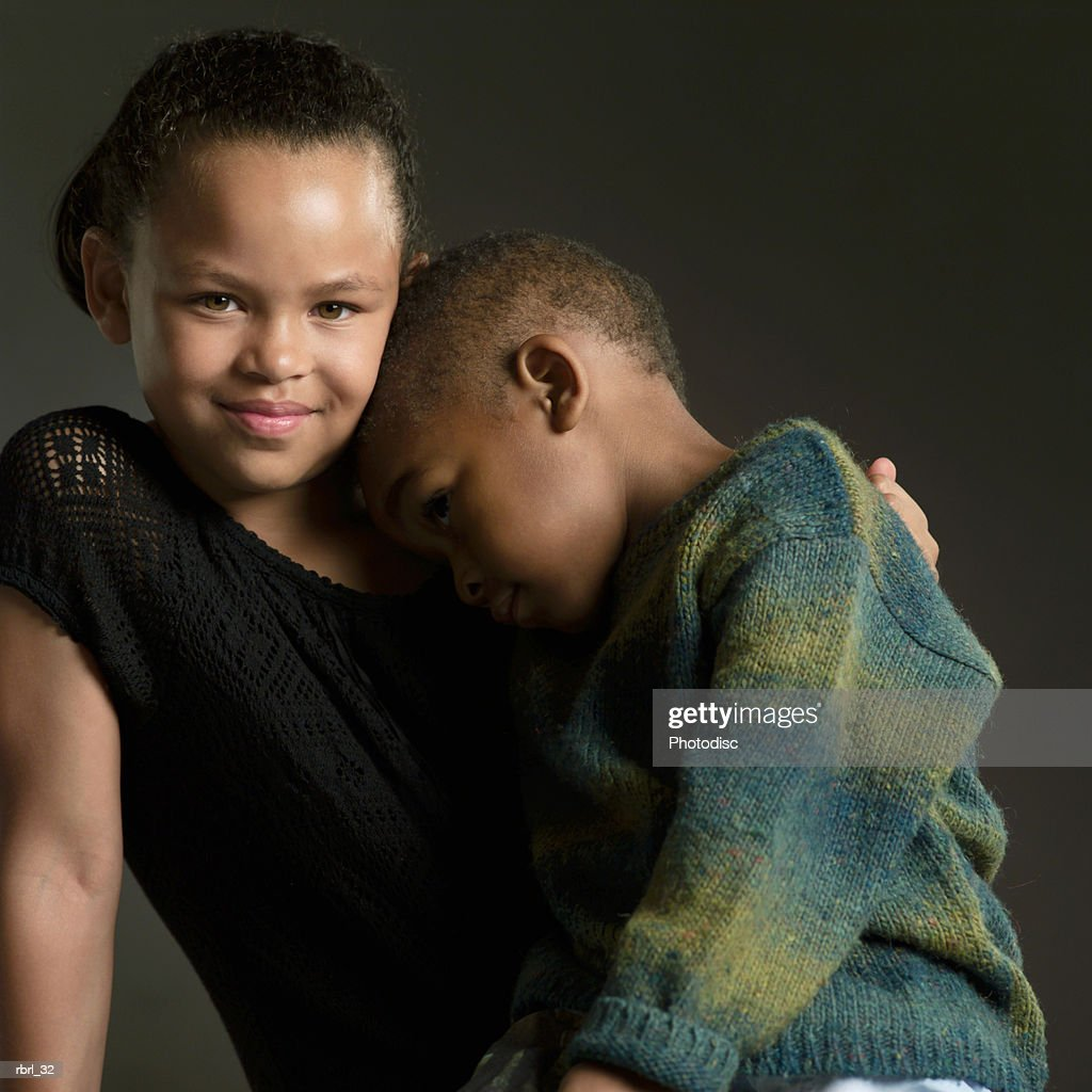 a cute african american female child smiles as she puts her arm around her little brother : Foto de stock
