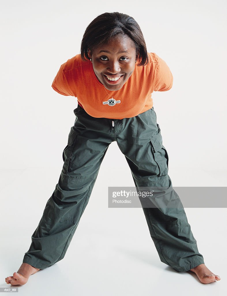 a cute african american teenage girl wearing an orange teeshirt is barefoot as she stands with legs spread and bends forward smiling at the camera : Foto de stock