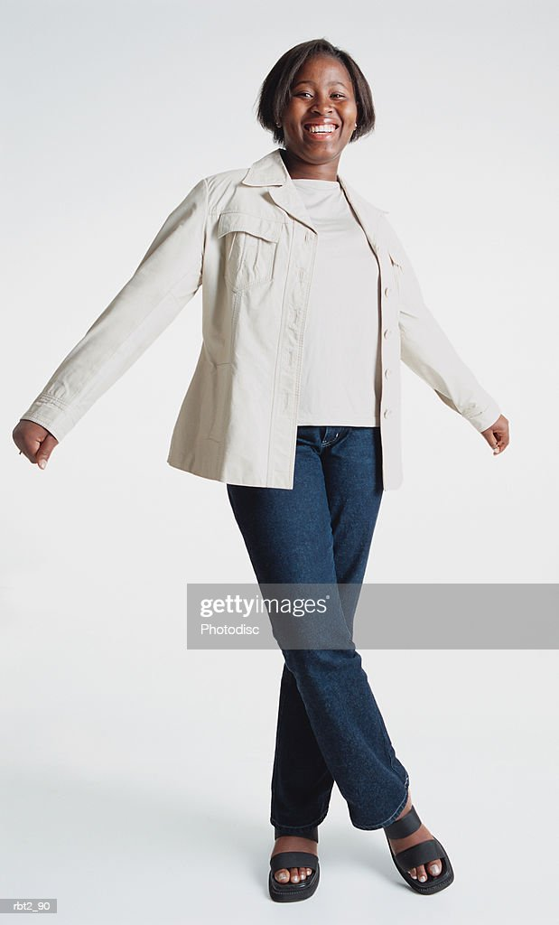a cute african american teenage girl wearing jeans and a white blazer is standing about to twirl around as she spreads her arms and one foot crosses over the other : Foto de stock