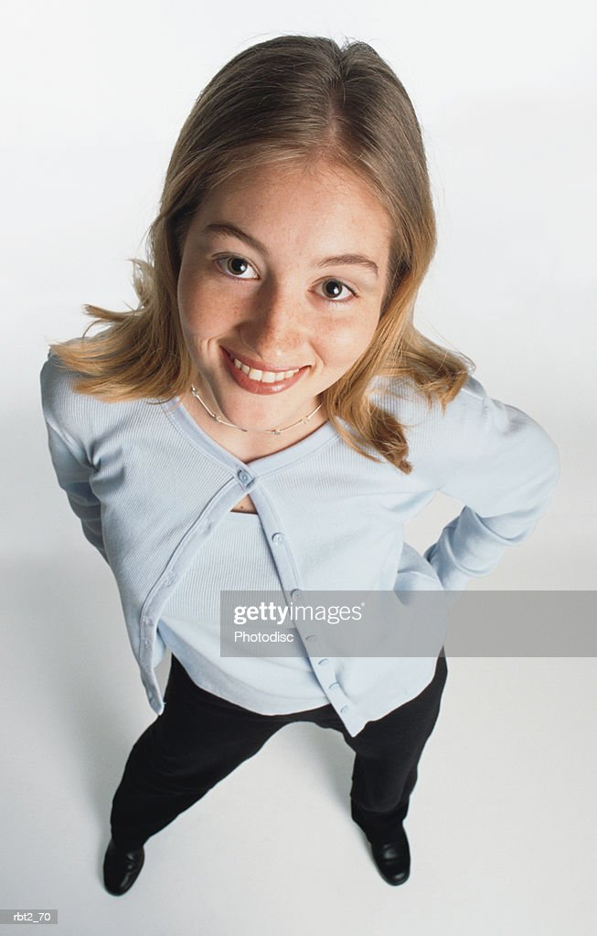 a cute blond cuacasian teenage girl wearing a light blue sweater set and black slacks smiles up at the camera : Foto de stock