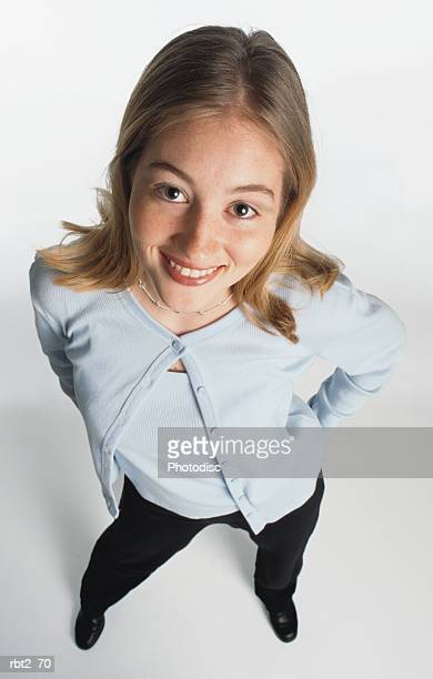 a cute blond cuacasian teenage girl wearing a light blue sweater set and black slacks smiles up at the camera - 若い女性一人 ストックフォトと画像