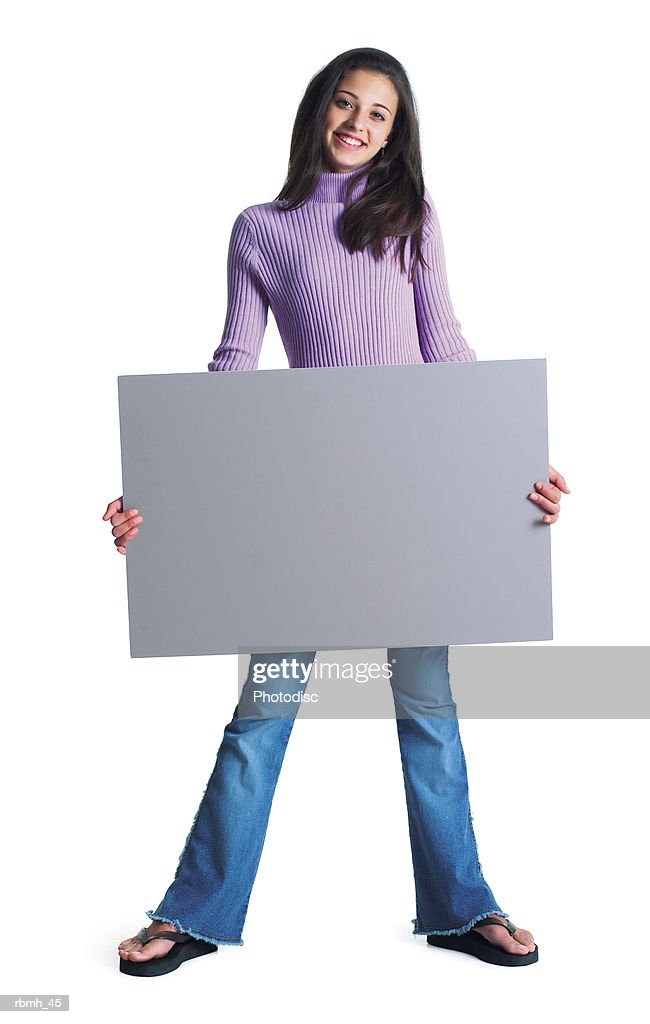 a cute ethnic female wearing jeans and a purple shirt stands with her feet shoulder width apart and holds a blank sign in front of her and smiles : Stockfoto